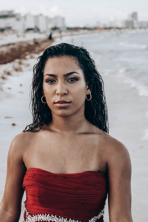 Emotionless ethnic female in glamorous dress with bare shoulders standing on wet sandy beach against blurred coastal town and looking at camera