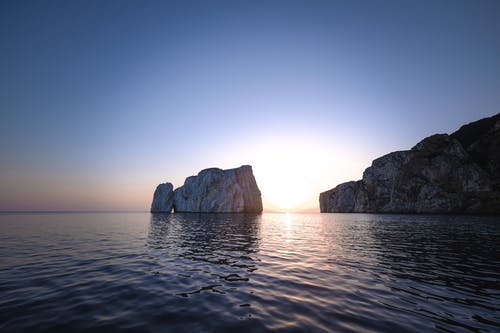 Majestic landscape of chalk cliffs in rippling sea water against cloudless sundown sky
