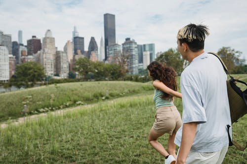 Side view of unrecognizable young female tourist holding hand of boyfriend and running in city park during romantic date in New York