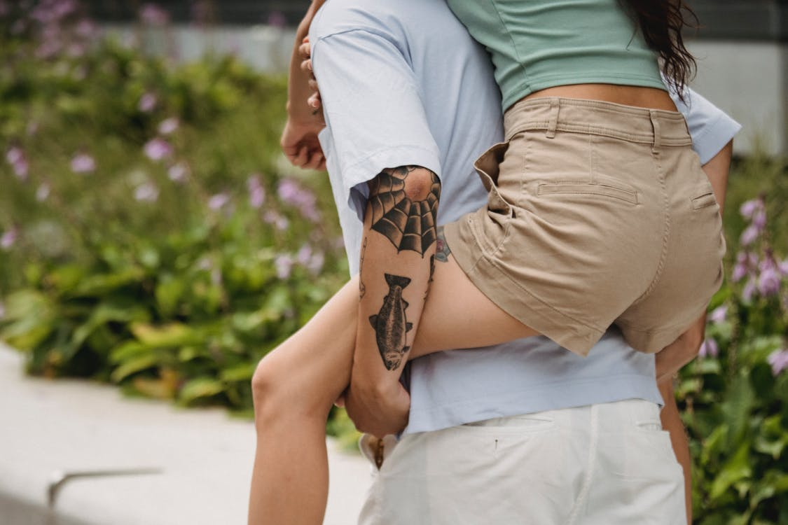 Back view of crop faceless young tattooed guy giving piggyback ride to slim girlfriend while spending time together in park on sunny day