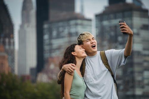 Freudiges Junges Asiatisches Paar, Das Kuschelt Und Lächelt, Während Es Selfie In Der Stadt Nimmt