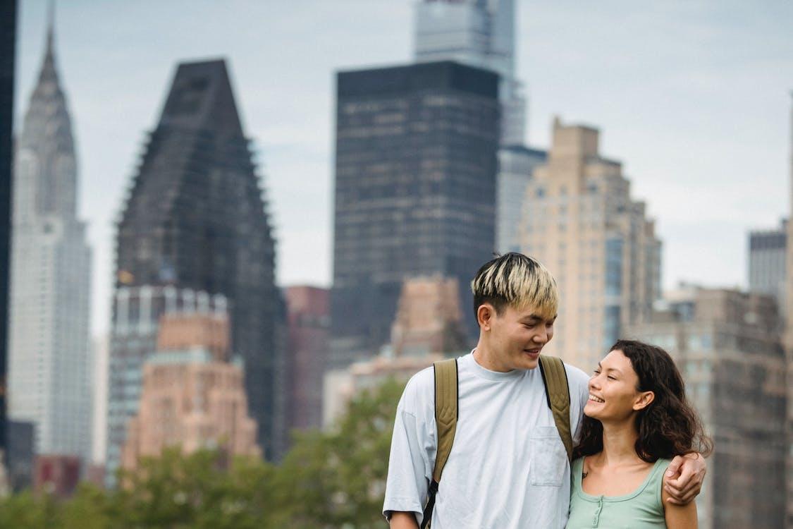Счастливая многонациональная пара обнимается в городском парке