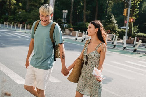 Cheerful young multiracial couple holding hands while crossing road during walk together in sunny day together
