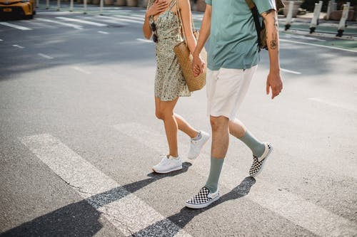 Crop anonymous couple holding hands walking on pedestrian crossing while spending time together in sunny city
