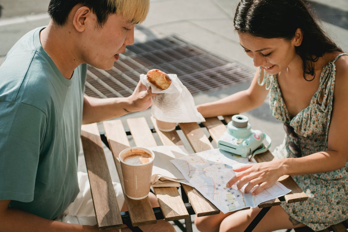 Diverse couple having breakfast in cafe while exploring map