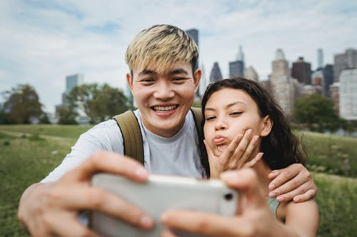 Cheerful Asian boyfriend hugging ethnic girlfriend making grimace while taking self portrait on cellphone in green city park