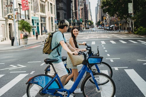 Asian couple with bicycles walking on crosswalk