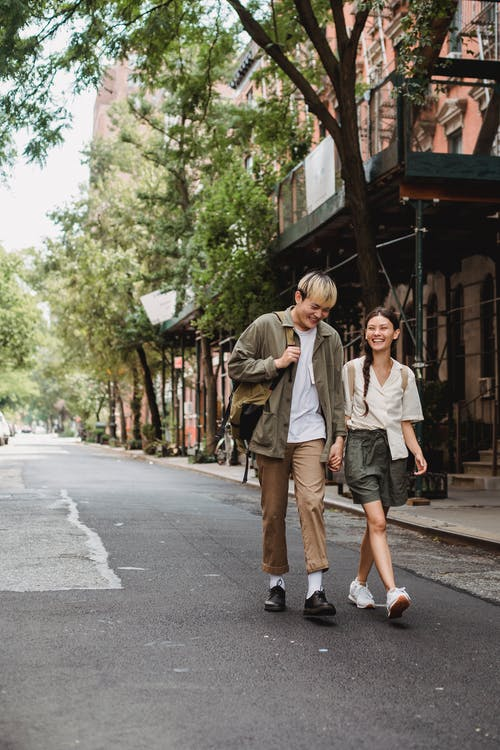 Cheerful Asian couple walking on street