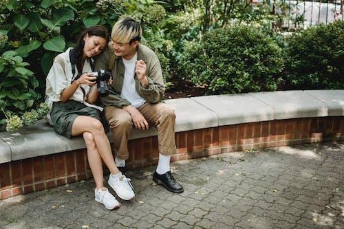Vrolijke Aziatische Paar Zittend Op De Bank Met Fotocamera