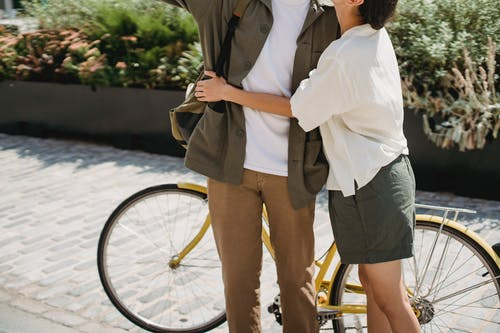 Unrecognizable loving couple in casual wear embracing while standing on pavement near bicycle and green plant in city on sunny street