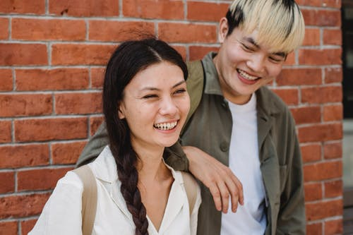 Delighted Asian boyfriend in casual wear with hand on shoulder of smiling girlfriend standing near brick wall on street in city