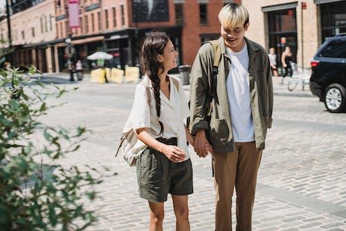 Delighted Asian couple walking on sidewalk