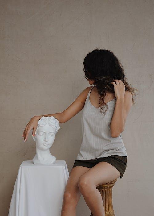 石の胸像の近くの流行の衣装で匿名の女性
