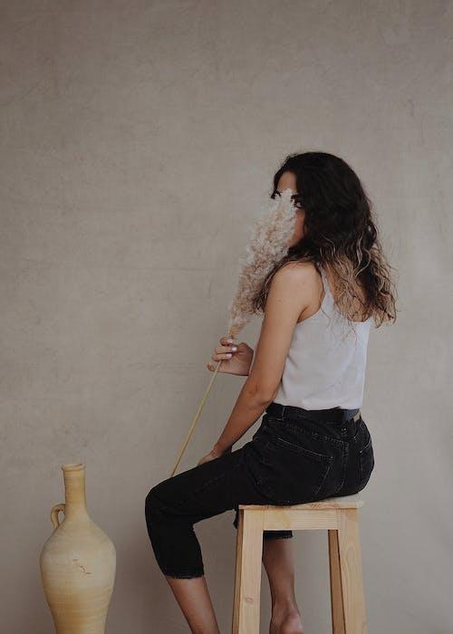 匿名的時尚女人遮住臉與壁附近的干燥植物