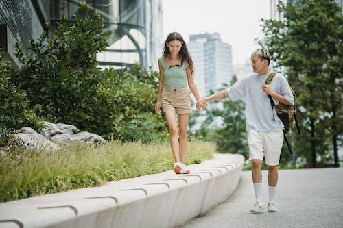 Happy Asian couple walking on street