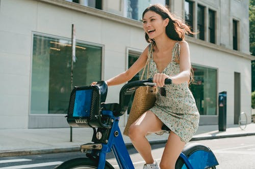 Happy young Asian lady smiling and riding bike on street