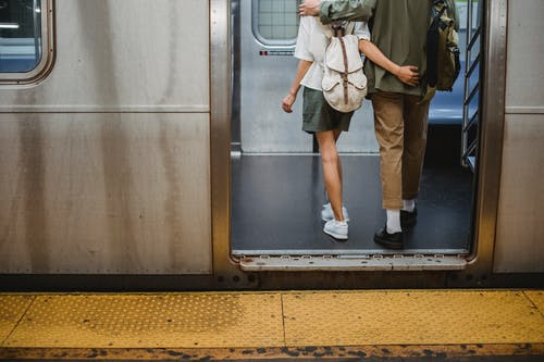 Back view of crop anonymous young couple in stylish outfits hugging while entering wagon of subway train