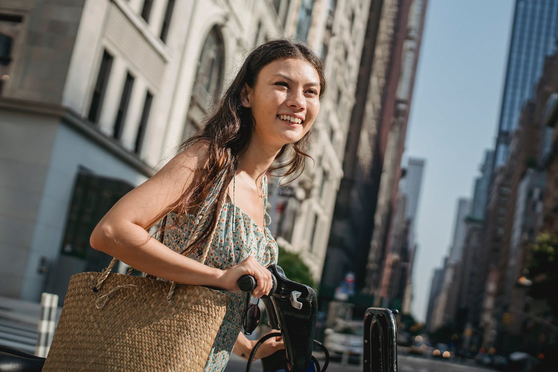 Sid view of happy young Asian lady with long dark hair in light dress standing near modern bike and smiling on sunny day in city downtown