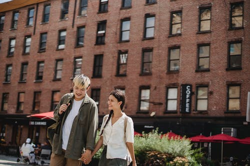 Cheerful young Asian couple in stylish clothes holding hands and smiling while walking in city during romantic trip
