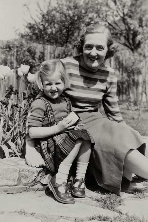 Grayscale Photo of Mother And Daughter Sitting on Concrete