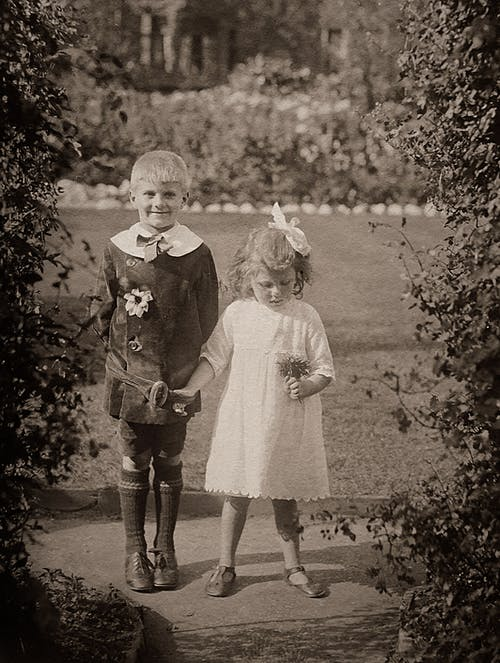 Adorable Boy And Girl Standing In The Garden