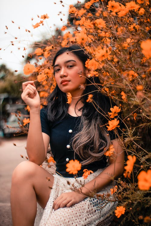 Woman Sitting next to Orange Flowers