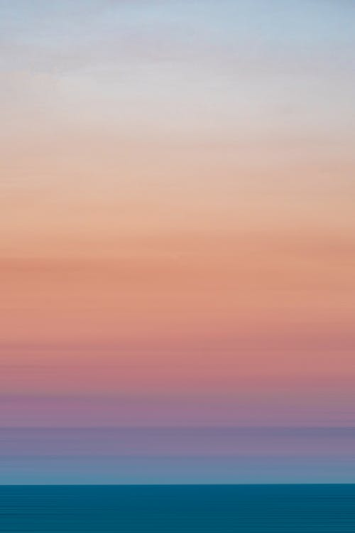 Light blue pink sky over silent ocean at sunset