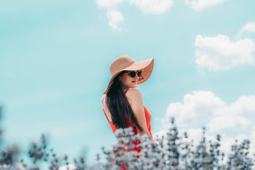 Woman in White and Red Floral Sleeveless Dress Wearing Brown Sun Hat