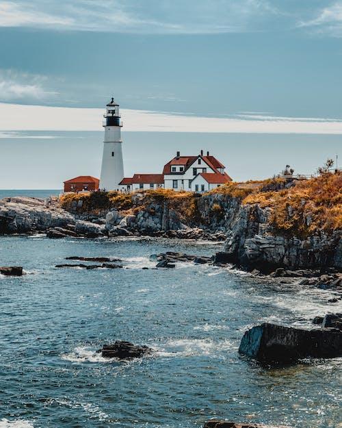 Lighthouse near sea on cloudy day
