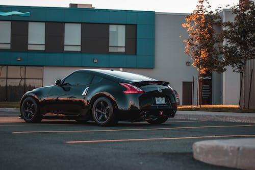 Stylish total black sport car near modern building