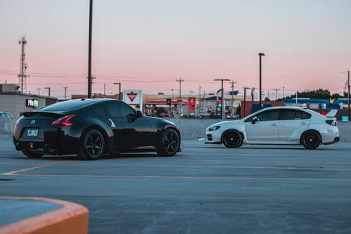 Stylish black and white sports cars parked on asphalt parking area in outskirts against cloudless sunset sky