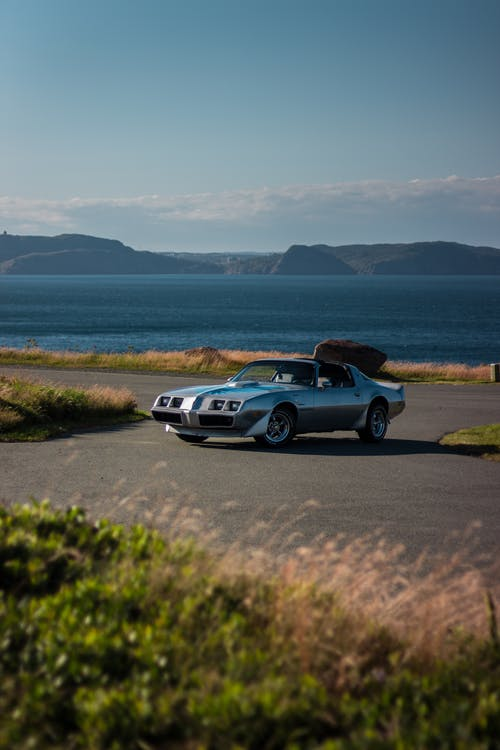 Old vintage sports car with unusual headlights on wide paved road for automobiles surrounded by verdant grass and reservoir near valley under light blue sky