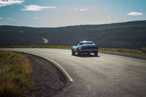 Car driving on empty roadwya in mountains