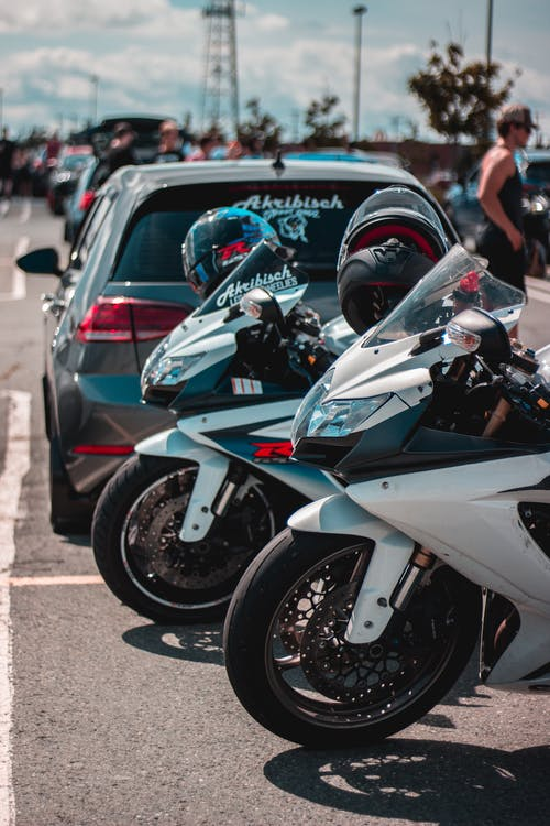 Motorcycles and cars on parking in daylight