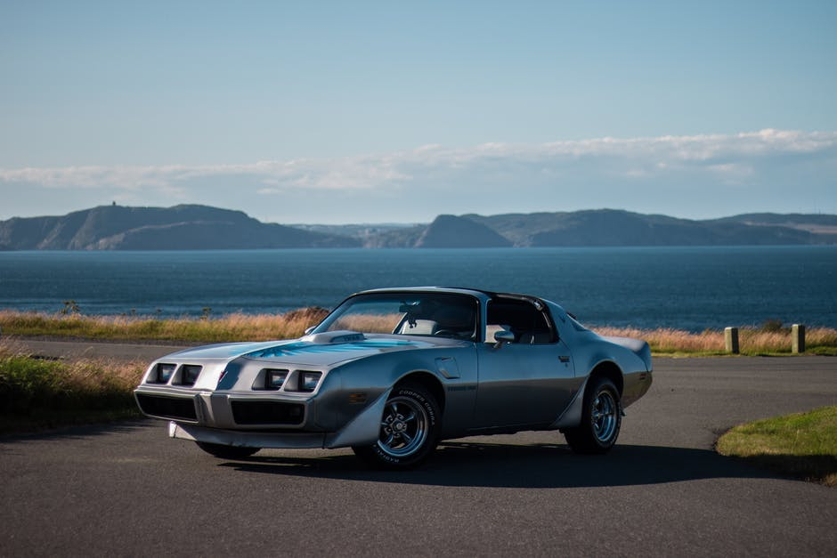 Vintage sports car parked on paved road near coast of lake