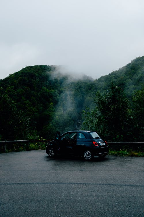 Car parked on roadside in verdant hilly nature