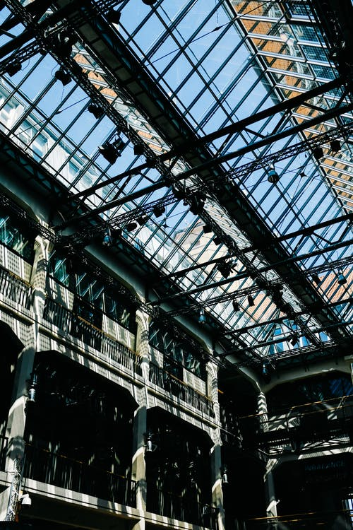 From below interior of contemporary mutistorey office building vestibule under transparent glass ceiling