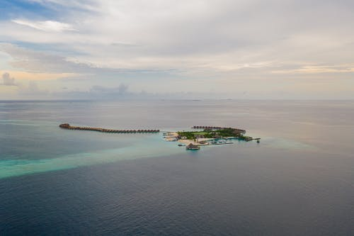 Drone view of small tropical island with peaceful resort surrounded by endless blue sea on clear weather