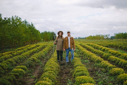 Couple with farm tools standing in field