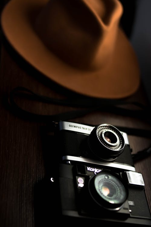 Vintage photo cameras placed on table with trendy hat