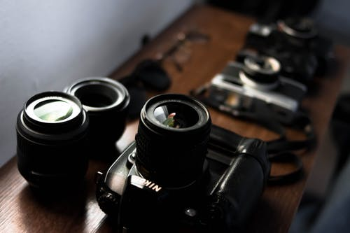 High angle collection of modern and retro photo cameras arranged on wooden table with professional lenses and sunglasses