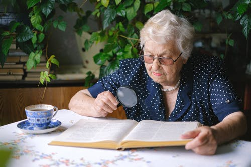 Focused senior woman reading with magnifier