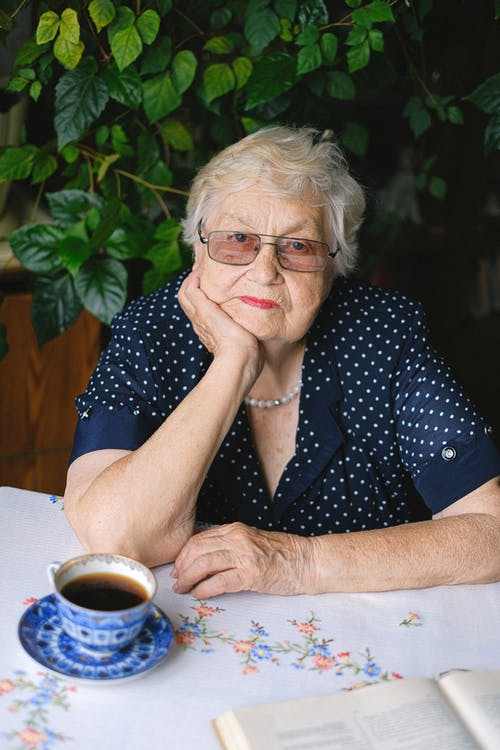 Senior woman sitting at table in room
