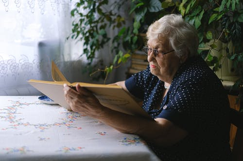 Side view of concentrated elderly female with gray hair and eyeglasses sitting at table and reading book at home with green plants