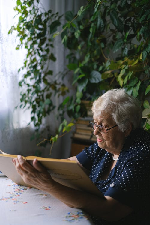 Elderly woman with book at home