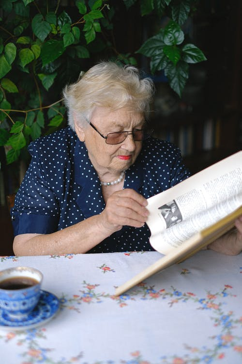 Focused senior woman reading book