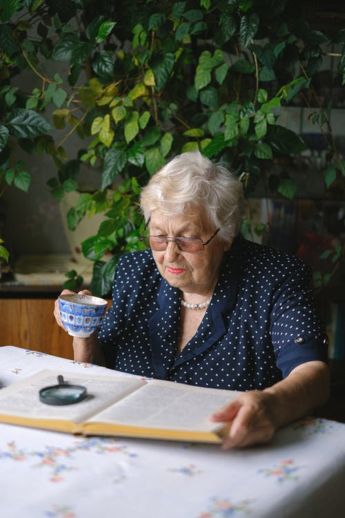 Serious elderly woman with cup reading book