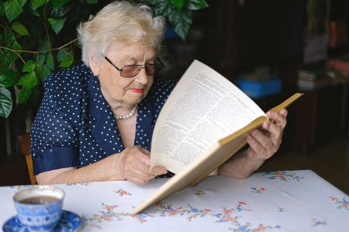 Focused aged woman turning pages of book