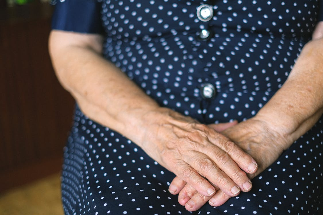 Unrecognizable old female wearing casual polka dot dress with folded wrinkled hands sitting at home in room on blurred background