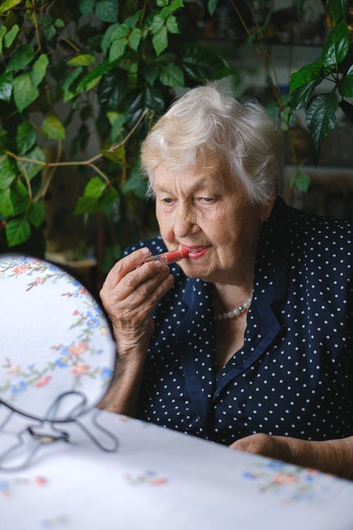 Senior woman applying lipstick in room